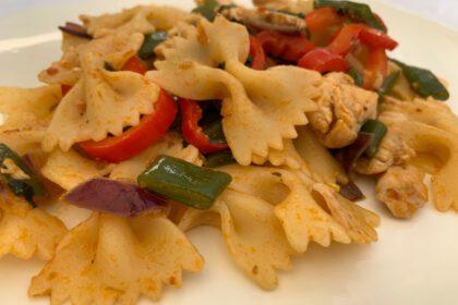 farfalle met kip, groenten en pesto arrabbiata foto